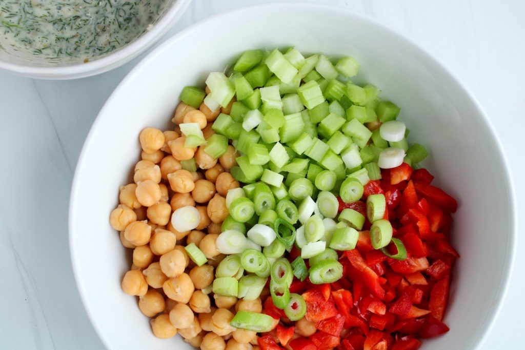 Displayed are ingredients to make a bean salad: chopped red pepper, celery, green onion with cooked chickpeas.