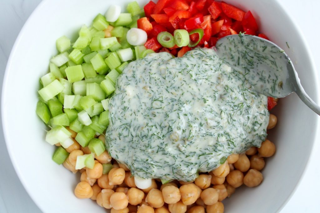 In a white bowl, you can see the ingredients to make a bean salad: chopped red pepper, celery, green onion and cooked chickpeas. There is a spoon topping the ingredients with the creamy yogurt and dill dressing.