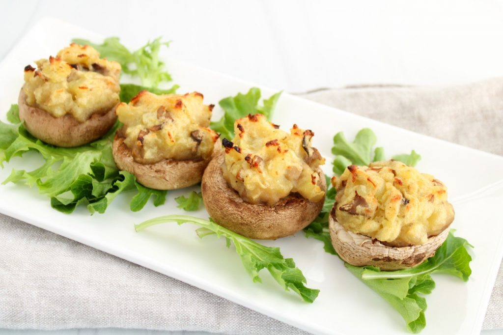 On a rectangular white plate, there are a few leaves of lettuce topped with 4 vegan stuffed mushrooms with mashed potatoes.