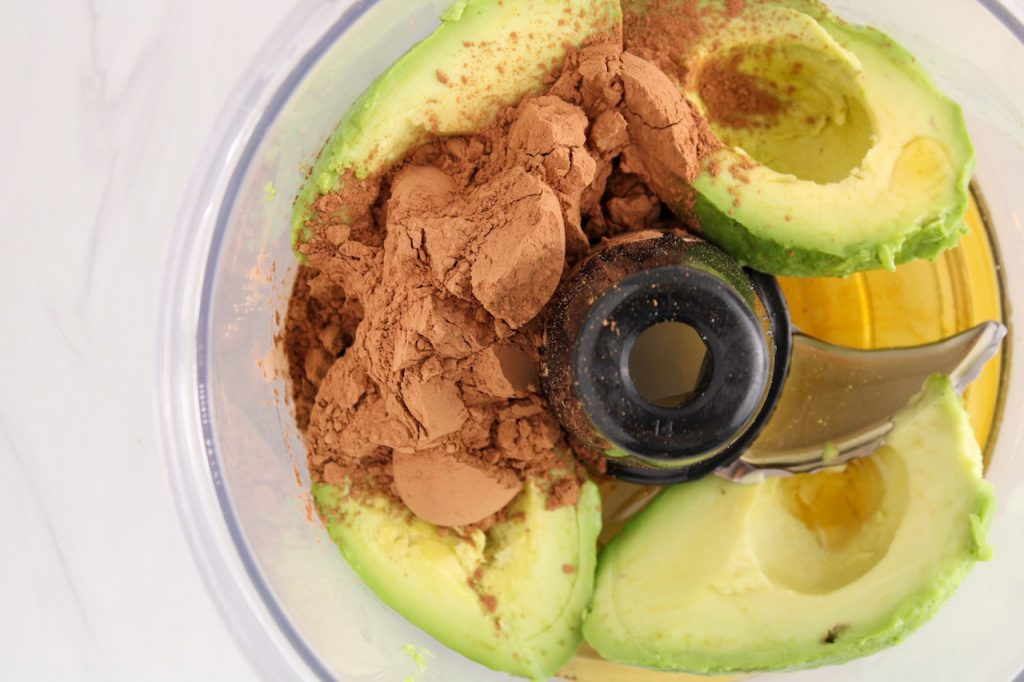 Close up on a food processor containing halves avocados, cacao powder and maple syrup.