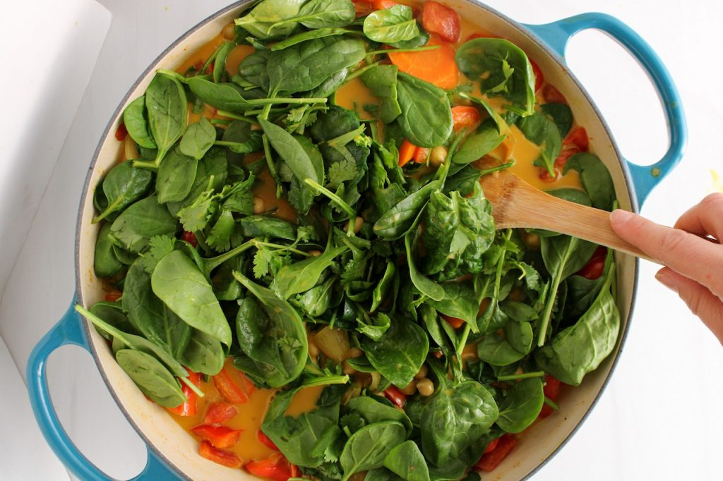 There is a wooden spoon stirring a mixture of vegetable in a yellowish broth: carrots, onion, red pepper and lots of spinach.