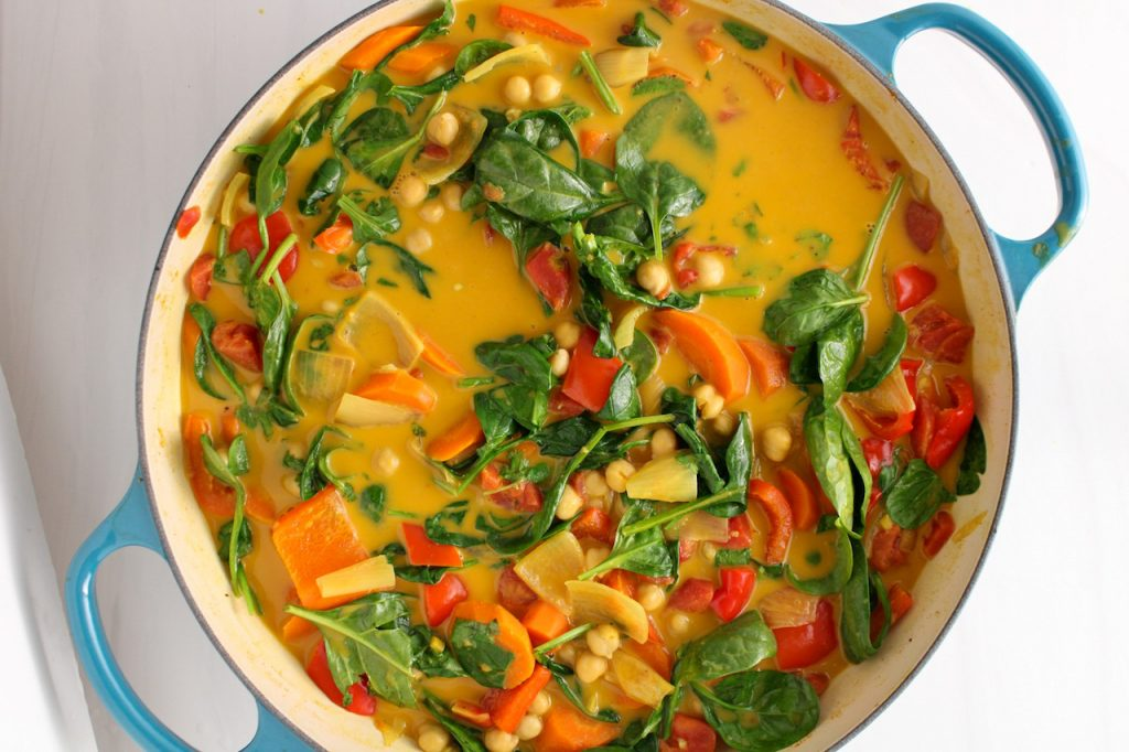 There is a large cast iron pan showing a mixture of vegetables (carrots, onion, spinach and red pepper) with chickpea that are soaking in a yellowish spiced broth.