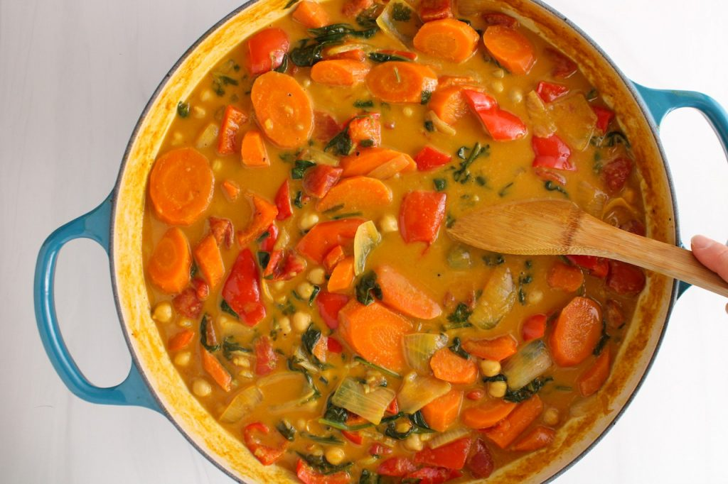 There is a wooden spoon stirring a curry stew containing carrots, onion, red pepper, spinach and chickpeas.