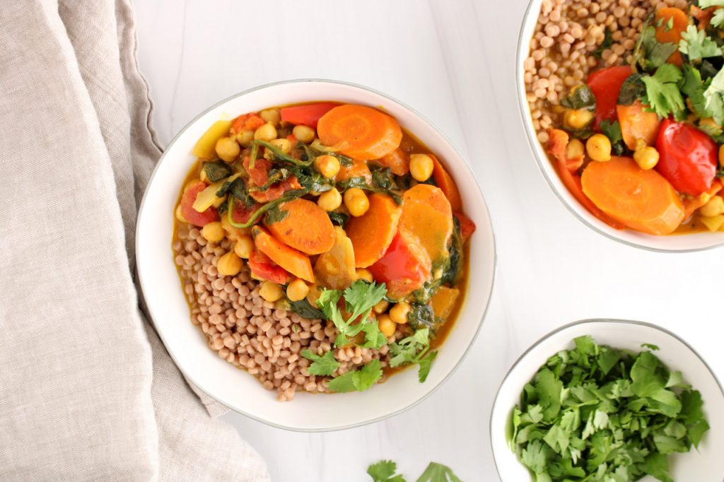 Showing is a white bowl containing Israeli couscous that is topped with a chickpea and spinach curry stew garnished with fresh cilantro. On the side, there is a beige hand towel and a small bowl with more fresh cilantro.