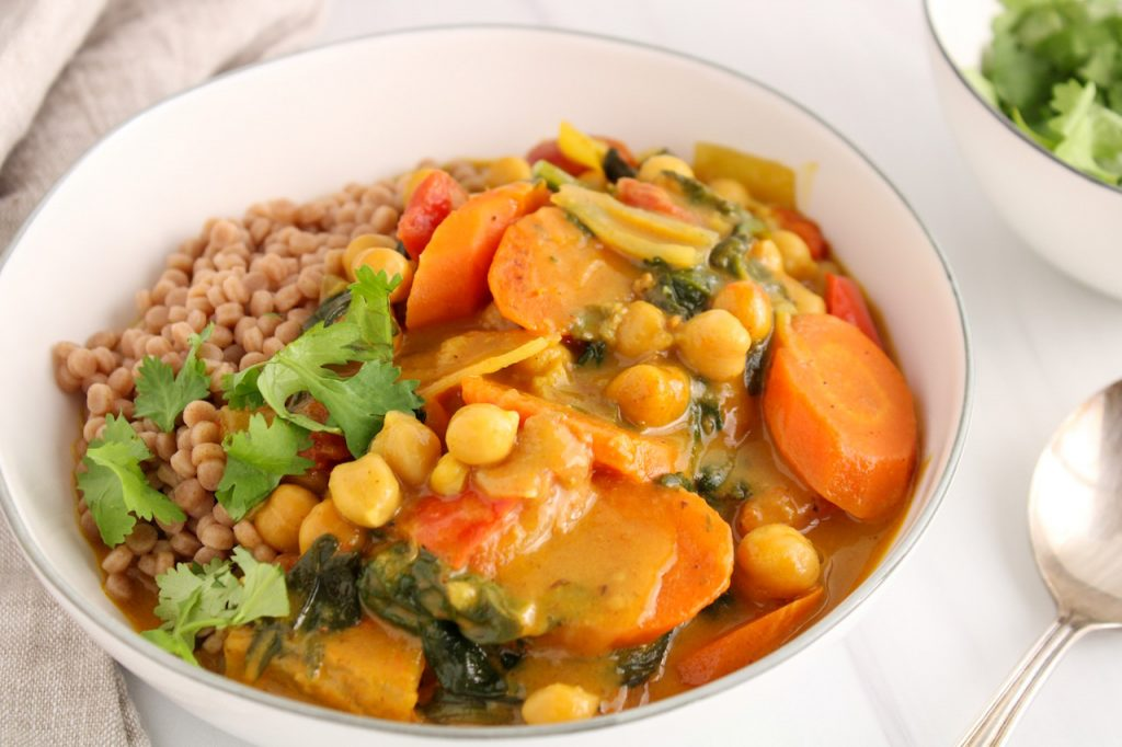 Showing is a white bowl containing Israeli couscous that is topped with a chickpea and spinach curry stew garnished with fresh cilantro. On the side, there is a large spoon, a beige hand towel and a small bowl with more fresh cilantro.