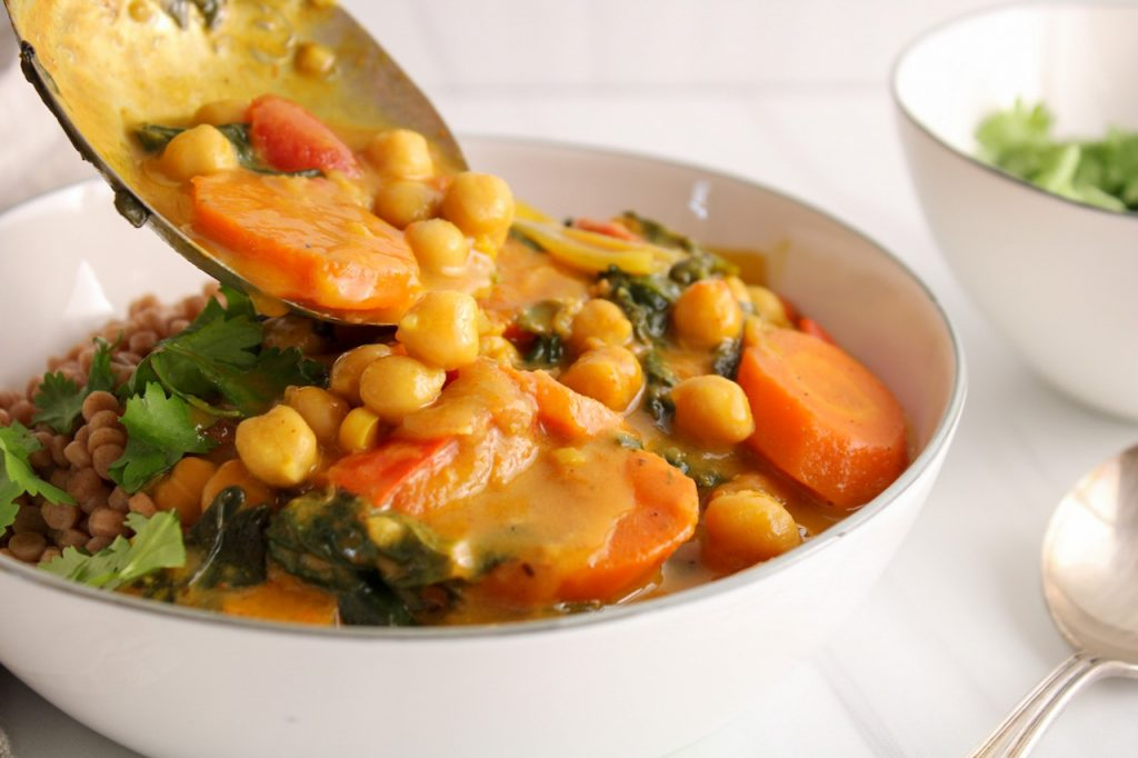 There is a large metallic serving spoon pouring some chickpea and spinach curry over Israeli couscous. There is a large spoon and a small white bowl containing some fresh cilantro.