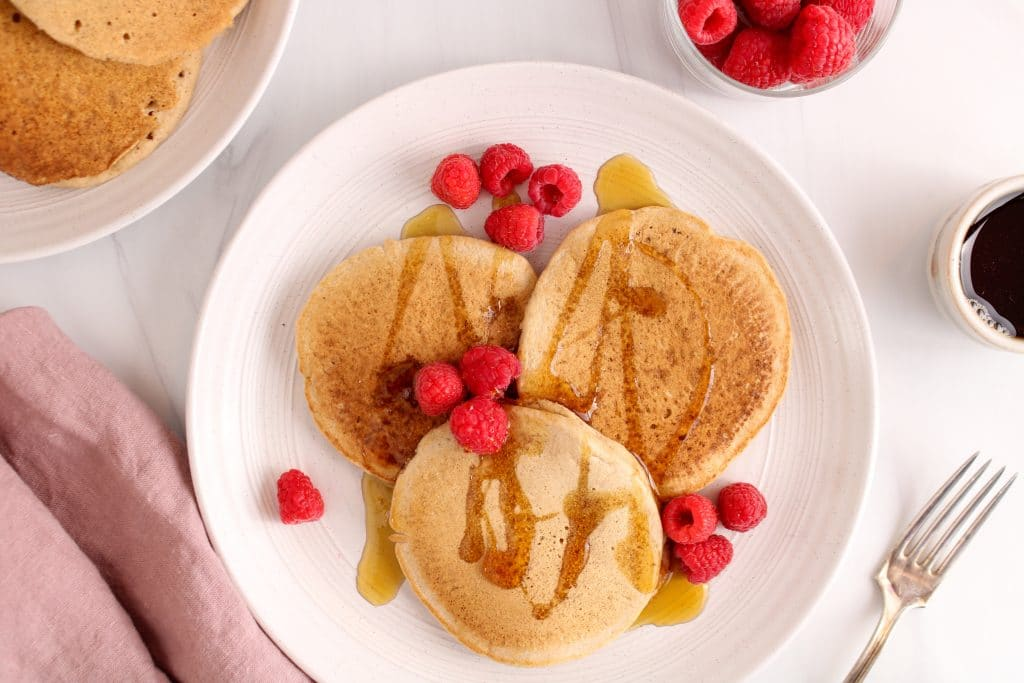 There are 3 oat flour pancakes on a large white plate with fresh raspberries and some maple syrup. On the side, you can see a fork, a pink hand towel, a small jar with more fresh raspberries, a small container with more maple syrup and another white plate with more of the pancakes.