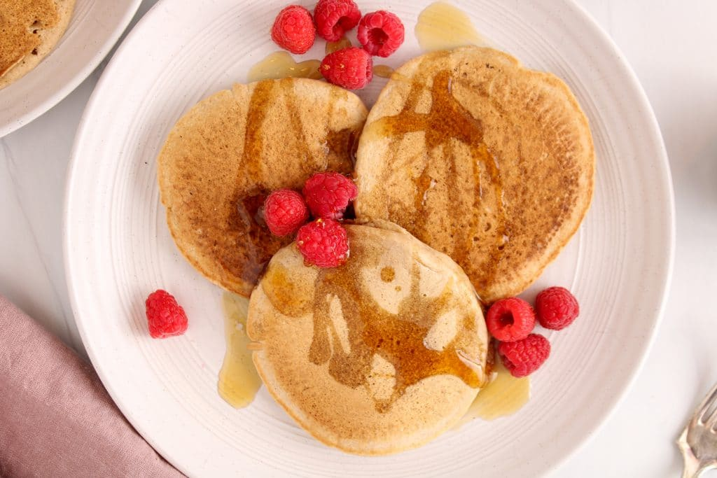 There are 3 oat flour pancakes on a large white plate with fresh raspberries and some maple syrup. On the side, you can see a fork, a pink hand towel and another white plate with more of the pancakes.