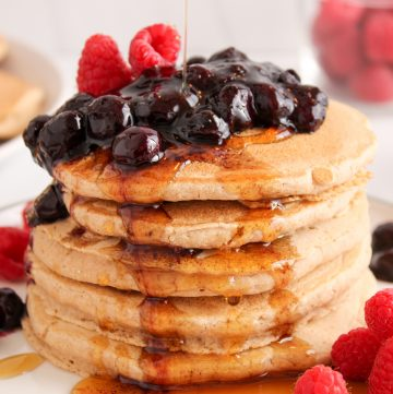 There are 5 oat flour pancakes stacked on top of each other on a white plates. There is a quick blueberry jam on top with some fresh raspberries and you can see some maple syrup being poured over the pancakes. Also on the side, there is a fork, a pink hand towel, a small container with maple syrup, a glass jar with fresh raspberries and a large white plate with more of the pancakes.