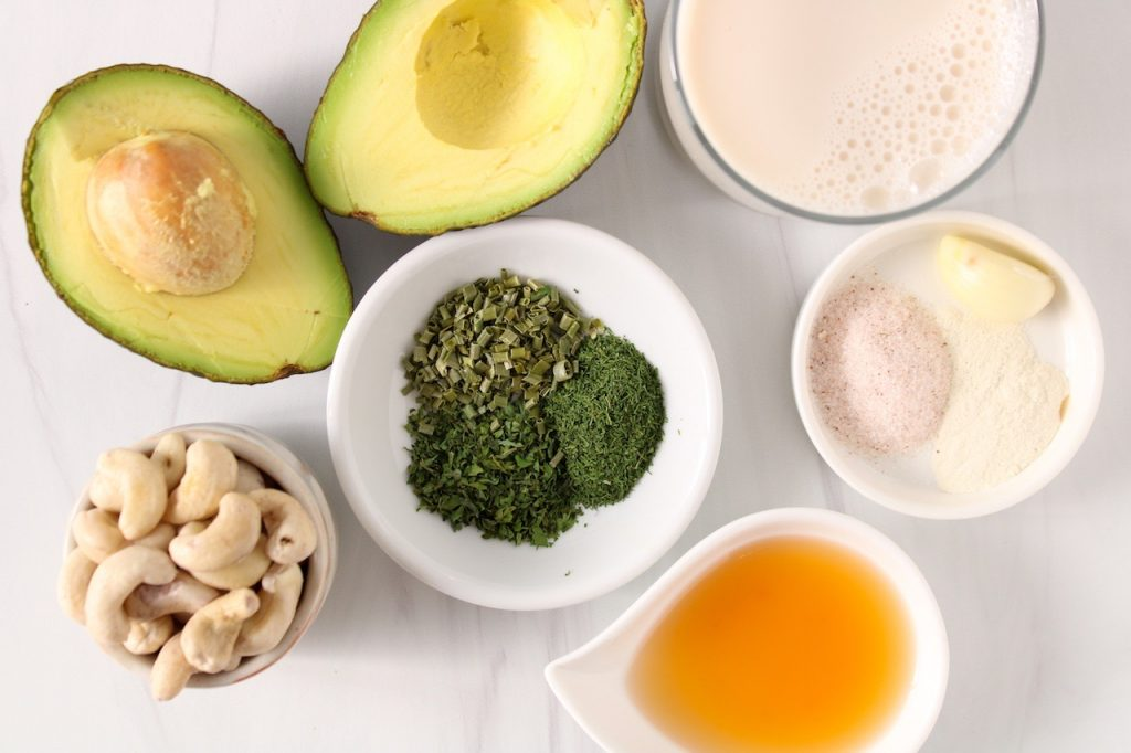 Displayed are the ingredients to make a vegan avocado ranch dressing: avocado, cashews, apple cider vinegar, salt, clove of garlic, vegan milk, onion powder and dried dill, parsley and chives.