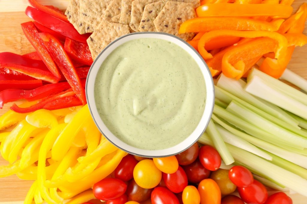 There is a green herby sauce in a small white bowl surrounded by crackers, sliced peppers, celery and cherry tomatoes.