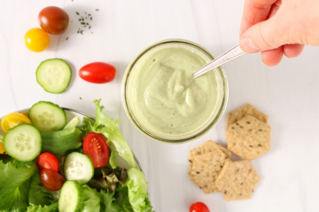 There is a vegan avocado ranch dressing in a jar with a hand holding a spoon into the sauce. On the side, there is a green salad with sliced cucumber and cherry tomato on a white plate and some crackers on the white table.