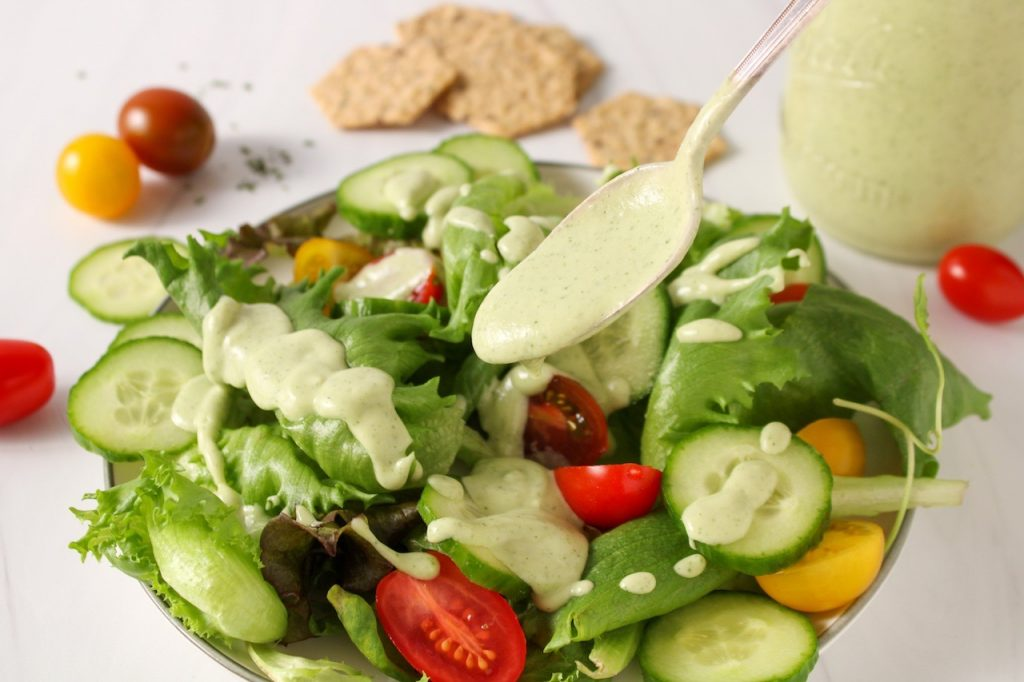 Showing is a green salad with cherry tomatoes and sliced cucumbers. There is a spoon drizzling some vegan avocado ranch dressing over the salad. In the background, there is a jar with more of the dressing and some crackers.