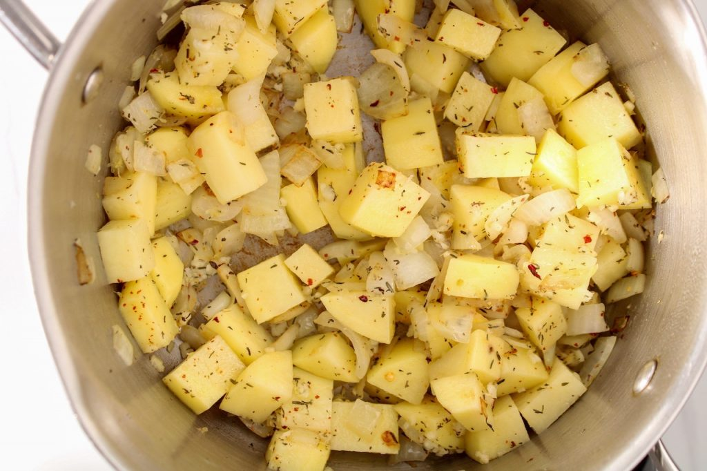 Diced potatoes are cooking in a stainless steel pot with dried thyme, onion and red pepper flakes.