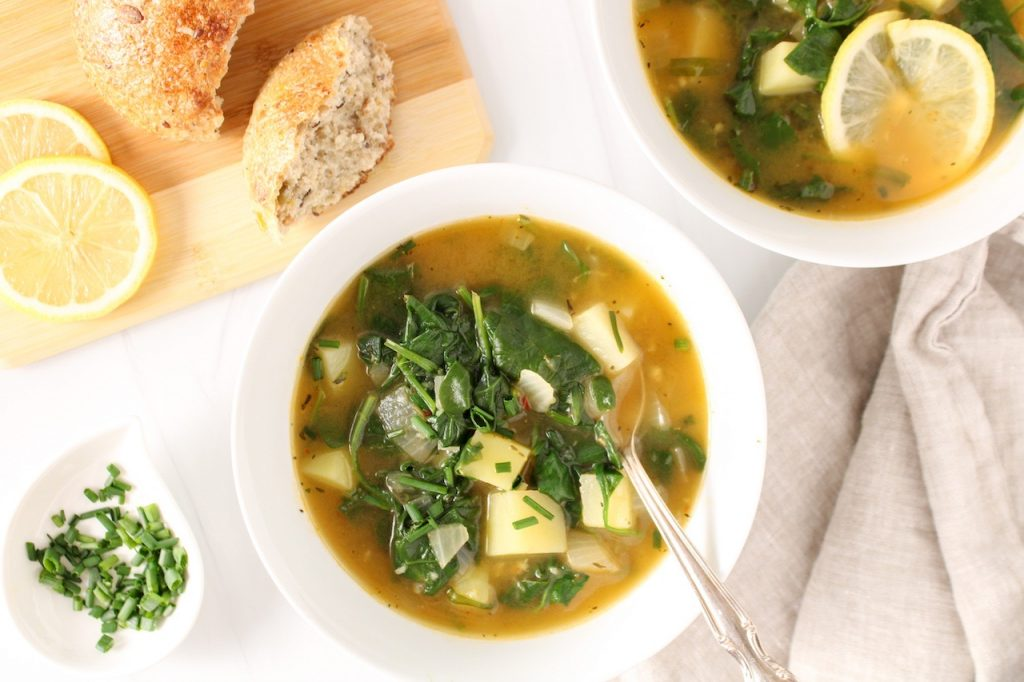 There are 2 white bowl containing a vegan spinach soup with potatoes. There is a small white bowl with chopped chives on the side, as well as a beige hand towel and a wooden board with sliced bread and lemon wedges.