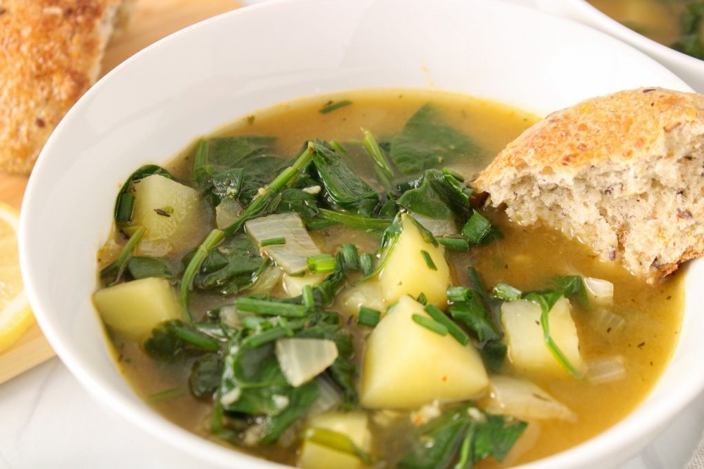 Close up on a vegan spinach soup made with potatoes with a piece of crusty bread being dipped in the soup.