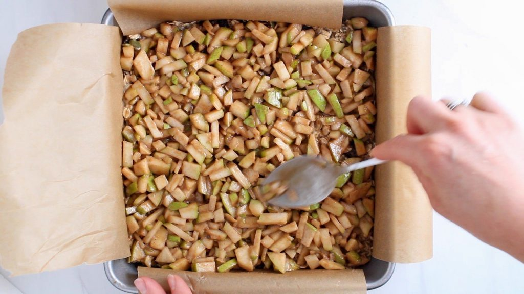 There is a spoon spreading a pear mixture over a oatmeal mixture in a square cake pan.