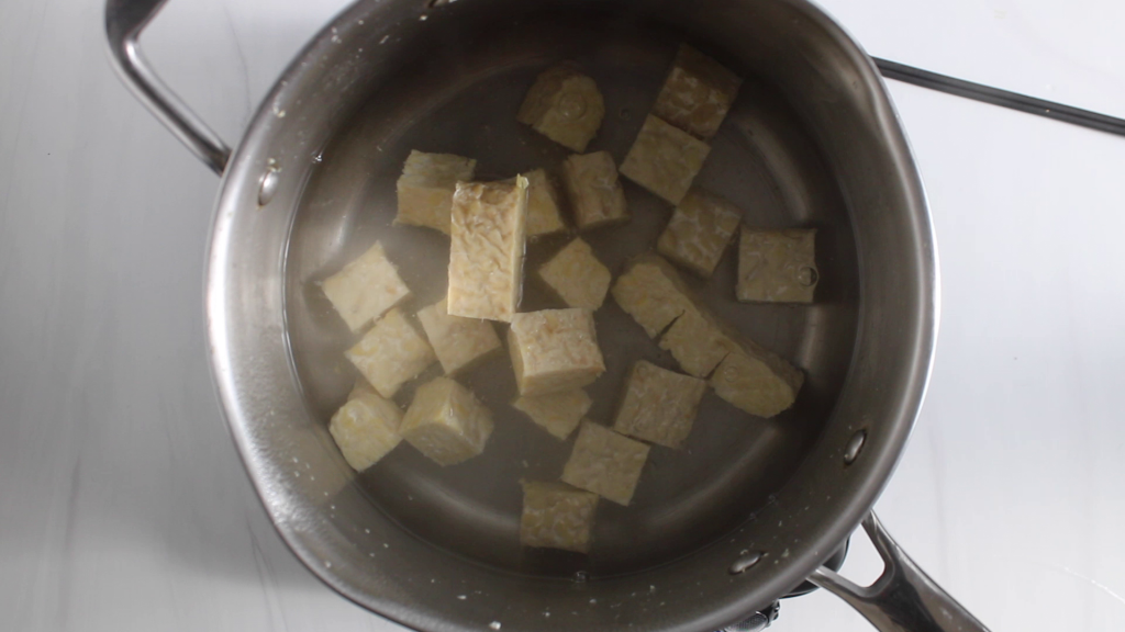 There are cubes of soybean product being boiled in water in a medium pot.
