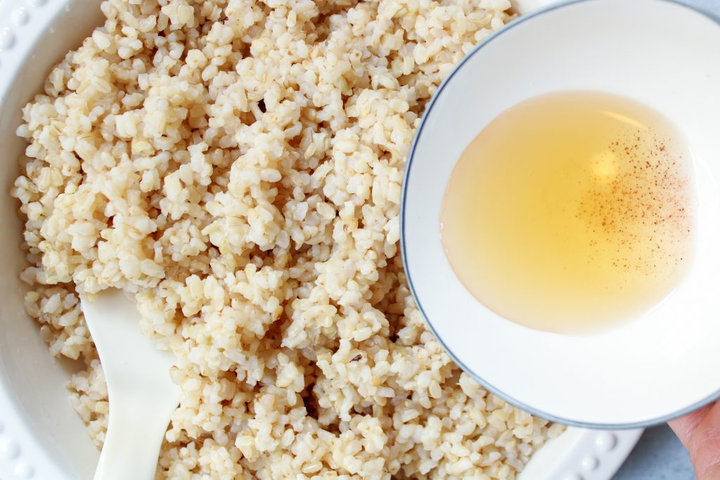 A large bowl contains cooked brown rice, with a rice spatula in it. On the side, a white bowl with sushi seasoning getting ready t be poured over the rice.