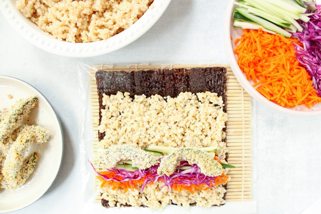 There is a sushi roll being built, you can show the sushi being being rolled containing a nori sheet, then topped with brown rice, shredded carrots, red cabbage, sliced cucumber and panko baked avocado. There are some of the vegetable in a bowl on the side, more panko baked avocado on a plate and more of the rice.