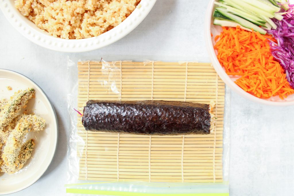 A sushi was just rolled and is displayed on a sushi mat. Also on the side: a large bowl of brown rice, an other bowl of cut veggies (carrots, cucumber, purple cabbage) and one more bowl containing avocado tempura.