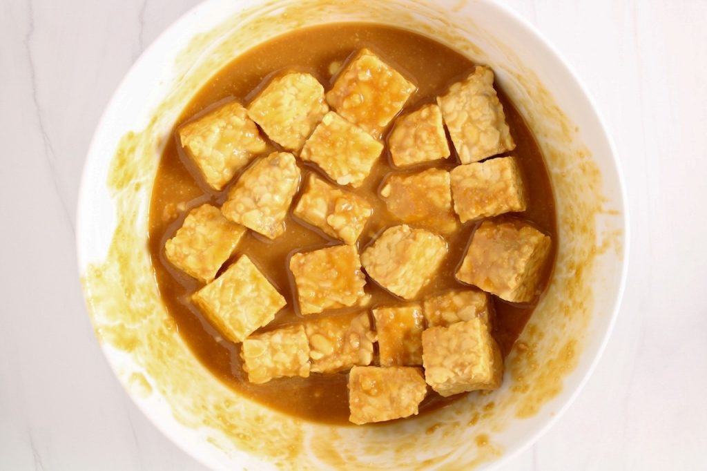 Showing are cubed of soybean product in a white bowl being soaked in a marinade that's made with miso paste.