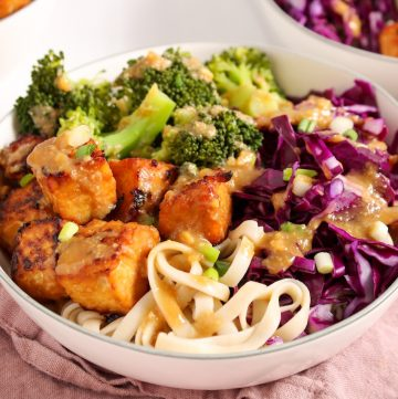 Showing is 2 white bowl (one you can only see half of it) containing brown rice noodles that are topped with miso tempeh, shredded red cabbage and steamed broccoli. There is a drizzle of a miso sauce on top as well as sliced green onion. On the table on the side, there is a pink hand towel, a fork and a small white bowl with more of the tempeh.