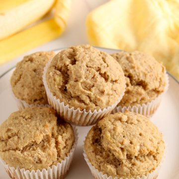 Showing is 5 vegan almond flour banana muffins pilled on a white plate. On the table beside the plate, there are a few bananas and a yellow hand towel. Also with an extra muffin on the towel in the background.