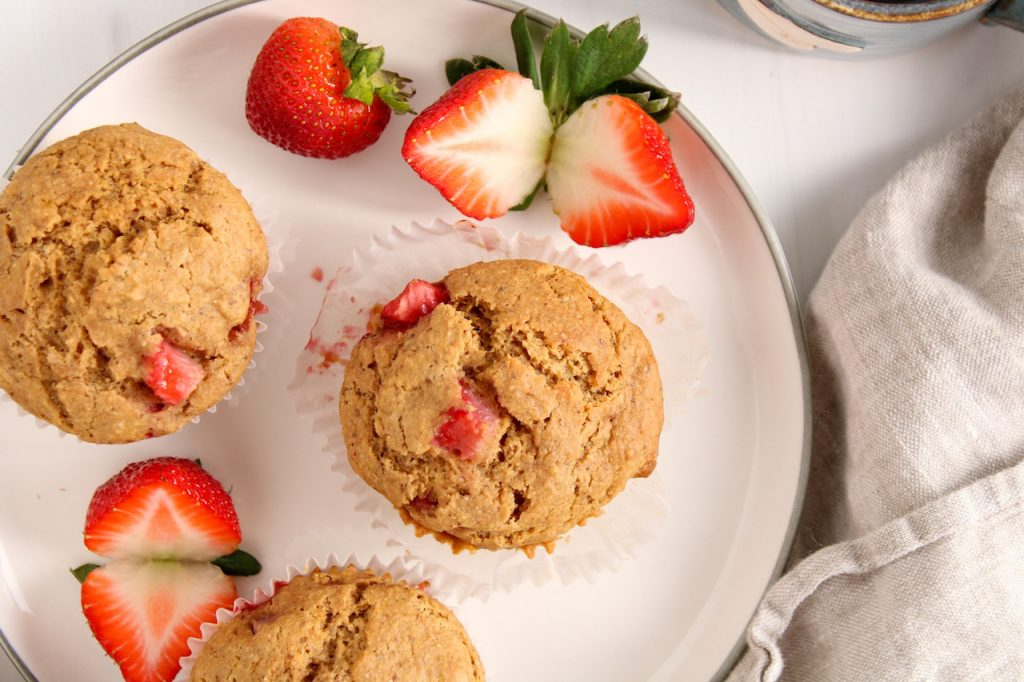 Showing are a few vegan strawberry muffins on a white plate with a few sliced strawberries. On the table on the side, there is a beige hand towel and a blue cup of tea.