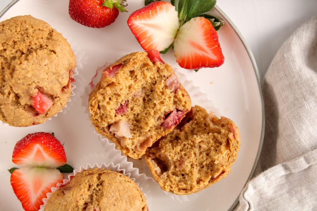 Close up on a vegan strawberry muffin that was cut in half. On the side on the plate, there is more muffins with sliced strawberries.