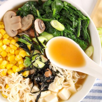 Showing is a miso ramen soup in a large white bowl that is topped with corn, wilted spinach, green onion, silken tofu and nori seaweed. You can see some of the ramen noodle floating beside all of the toppings as well as a few pieces of sliced mushrooms. There is also a white Asian style spoon on top on the noodle hanging on top.On the table on the side, there is a lined white an blue hand towel and a wooden cutting board with green onions.