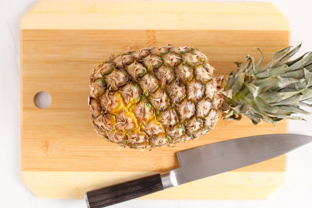 Showing is a whole pineapple displayed on a cutting board with a large silver knife on the side.