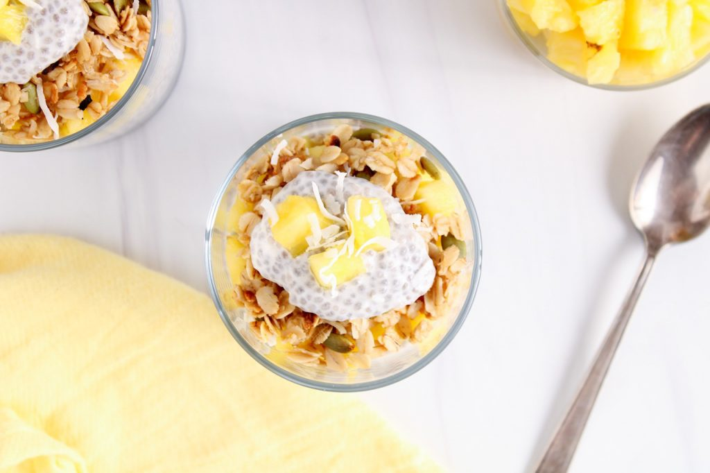 Close up (over head shot) of a chia seed parfait with on the side a yellow hand towel, a spoon, a jar with more diced pineapple and another parfait.