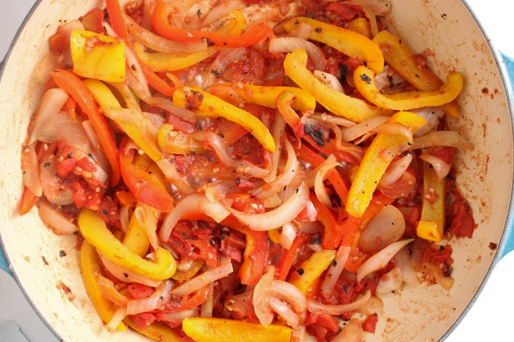 Showing is inside a large pan with sliced onion, red and yellow pepper being cooked with garlic and canned tomatoes.
