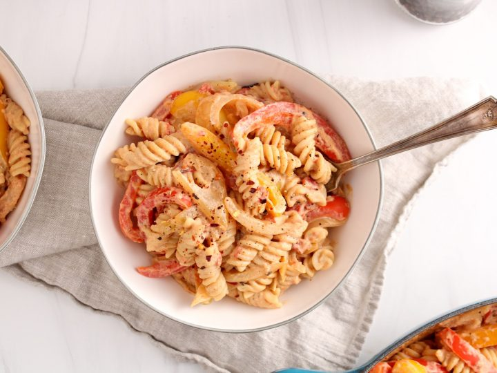 Showing is a white bowl containing vegan cajun pasta with a fork inside the dish. The bowl is on a beige hand towel. There is a black pepper grinder in the background as well as another bowl with the noodle