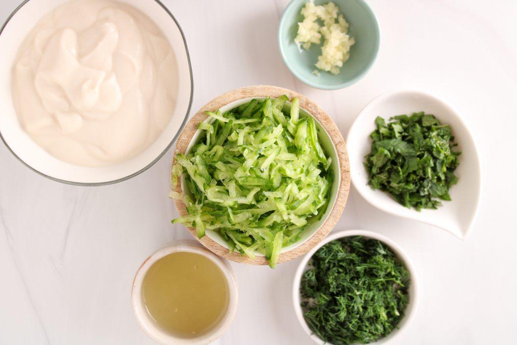 Ingredients needed to make a vegan Tzatziki, showing are vegan yogurt, shredded cucumber, garlic, lemon juice, fresh dill, fresh mint.