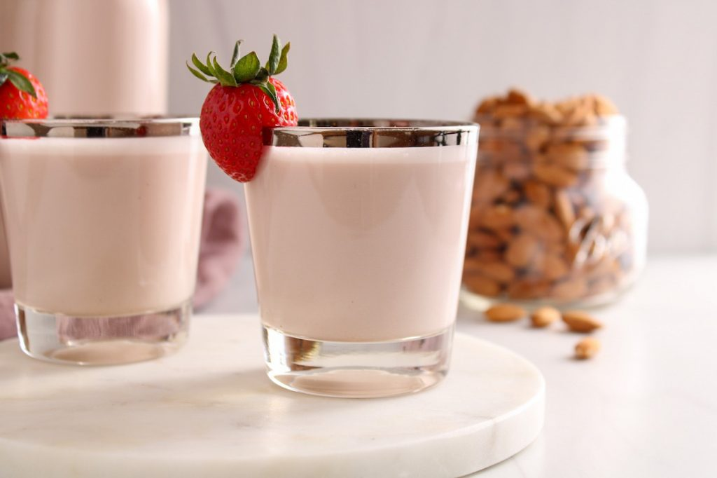 A small see through glass contains strawberry almond milk with a piece of strawberry hanging on the side of the glass. You can see one more glass of milk and raw almond in a glass container in the background