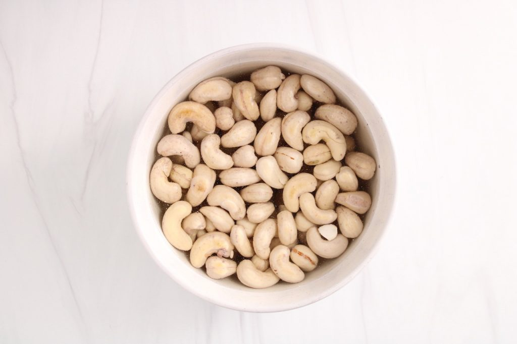 There are raw cashews soaking in a water in a white bowl.