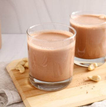 Showing are 2 small glasses containing a homemade cashew chocolate milk on a small wooden board placed over a beige hand towel. There are a few cashews on the side and a large jar with more of the milk.