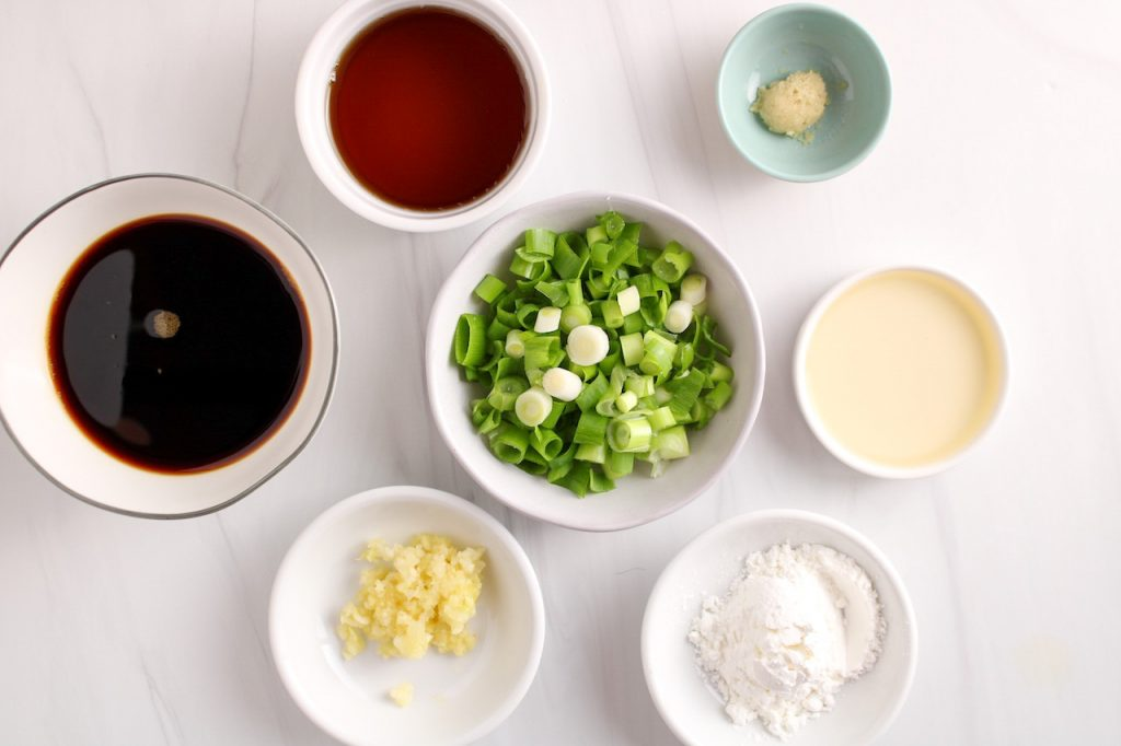 Showing are the ingredients needed to make a homemade teriyaki sauce displayed in small white bowls. There are soy sauce, rice vinegar, maple syrup, garlic, ginger, green onion and cornstarch.