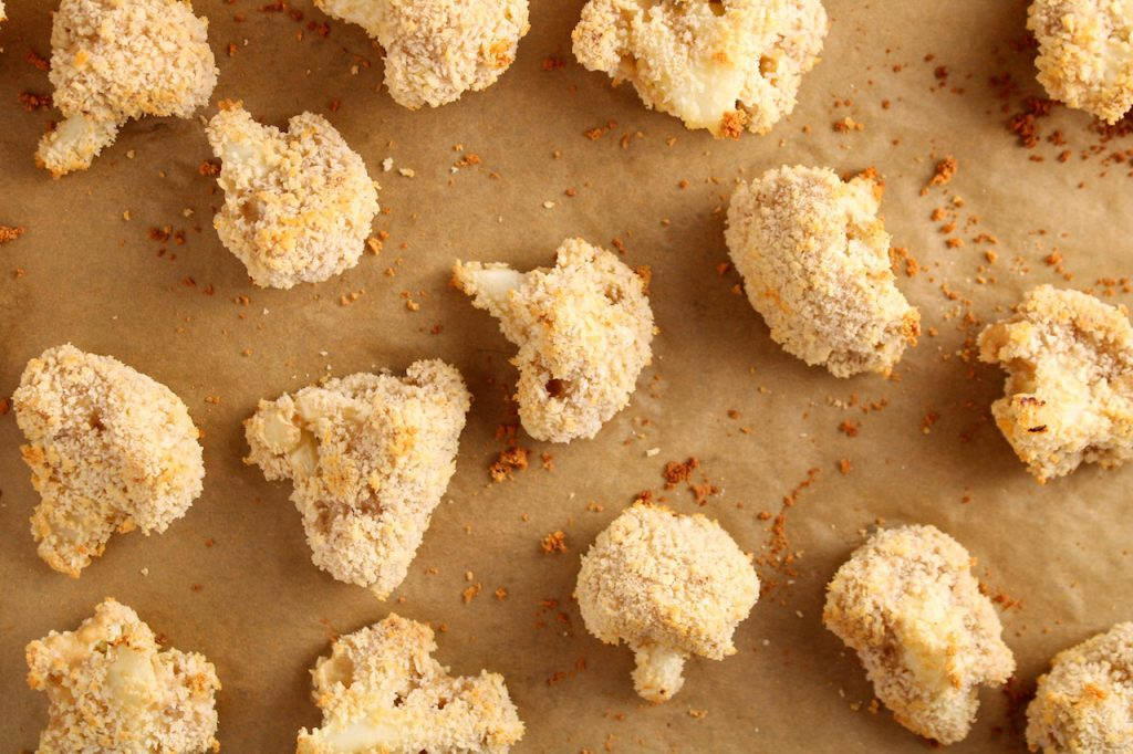 There are battered and panko covered floret of cauliflower on a parchment paper covered baking sheet that just got out of the oven.