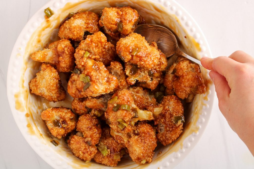 There are breaded vegetable being tossed in a Asian sauce in a white bowl. You can see a hand holding on a spoon and stirring.