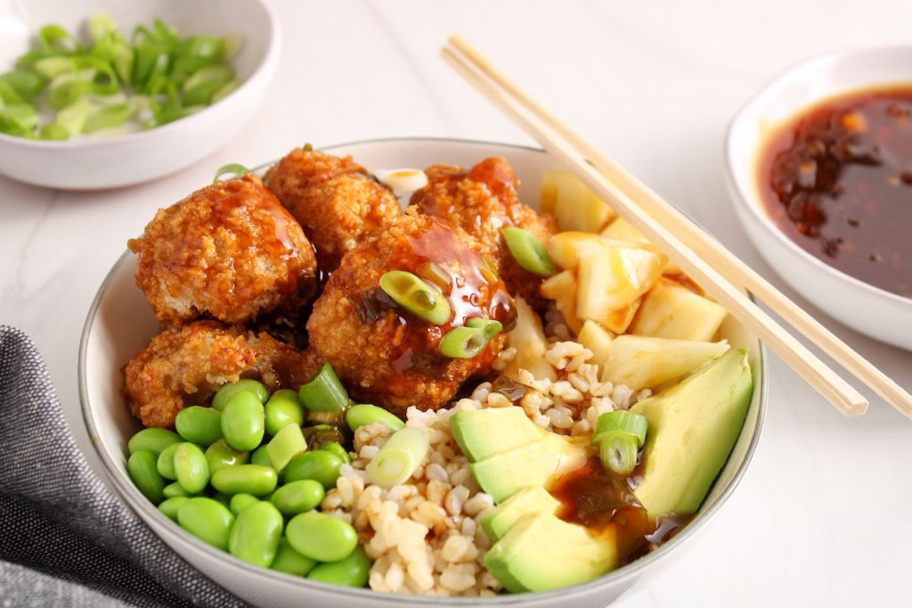 Showing are teriyaki cauliflower bites garnishing a rice bowl with avocado, edamame, pineapple and green onion. In the background, there is a bowl with more teriyaki sauce and sliced green onion.