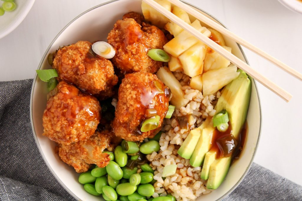 Showing are teriyaki cauliflower bites garnishing a rice bowl with avocado, edamame, pineapple and green onion. On the side, there is a grey hand towel and a set of chopsticks on the side of the bowl.