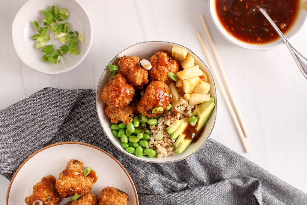 Showing are teriyaki cauliflower bites garnishing a rice bowl with avocado, edamame, pineapple and green onion. On the side, there is a grey hand towel and a set of chopsticks on the side of the bowl. You can also see more of the sauce, sliced green onion and more cauliflower bites on the side of the bowl.