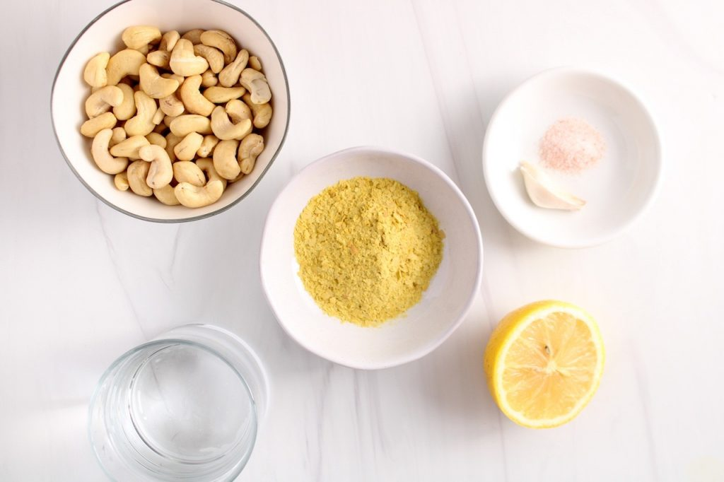 There a few white bowls containing water, raw cashews, nutritional yeast, a clove of garlic, half of a lemon and salt.