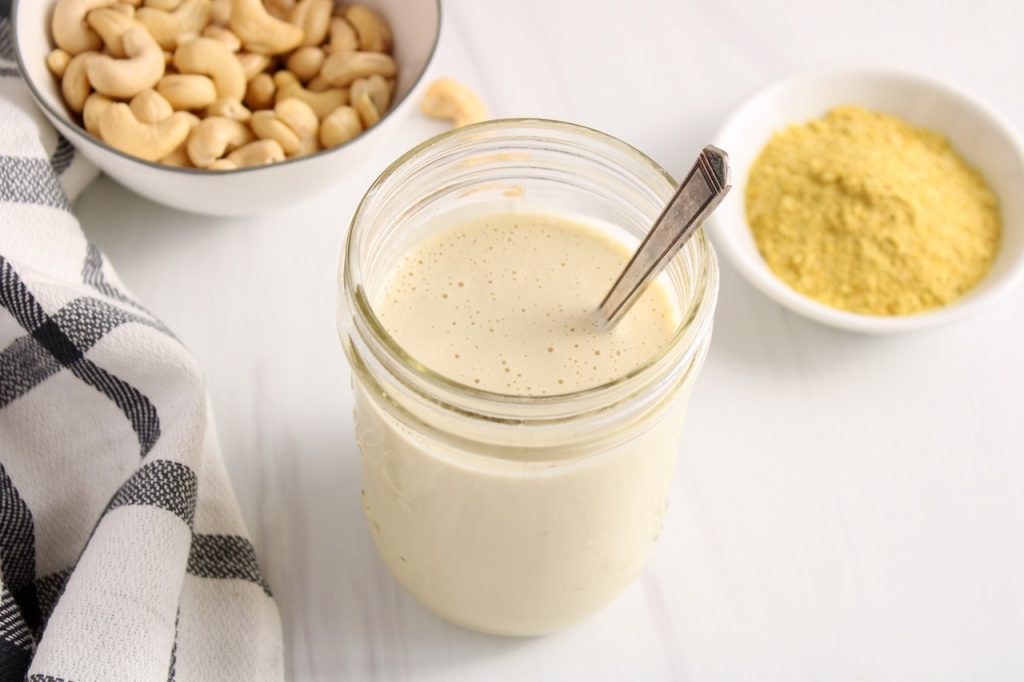 There is a see through jar containing a vegan white sauce with a spoon inside. In the background, there is nutritional yeast in a white bowl, raw cashews and a white and black hand towel.
