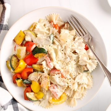 There is a large shallow white bowl with farfalle pasta mixed with a vegan white sauce and roasted pepper and zucchini. On the side, these is a black and white hand towel, a small white bowl with red pepper flakes, lemon wedges and another bowl with more pasta.
