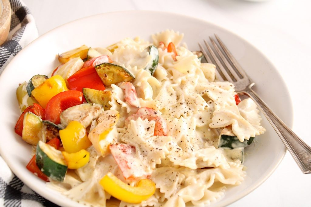 Close up on a white bowl containing farfalle pasta with a vegan white sauce and roasted pepper and zucchini.