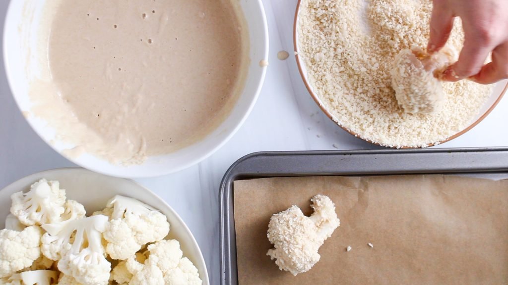 There is a hand breading cauliflower floret. You can see a bowl with the batter, a plate with panko, a bowl with the floret to be breaded and a baking sheet with the breaded cauliflower.